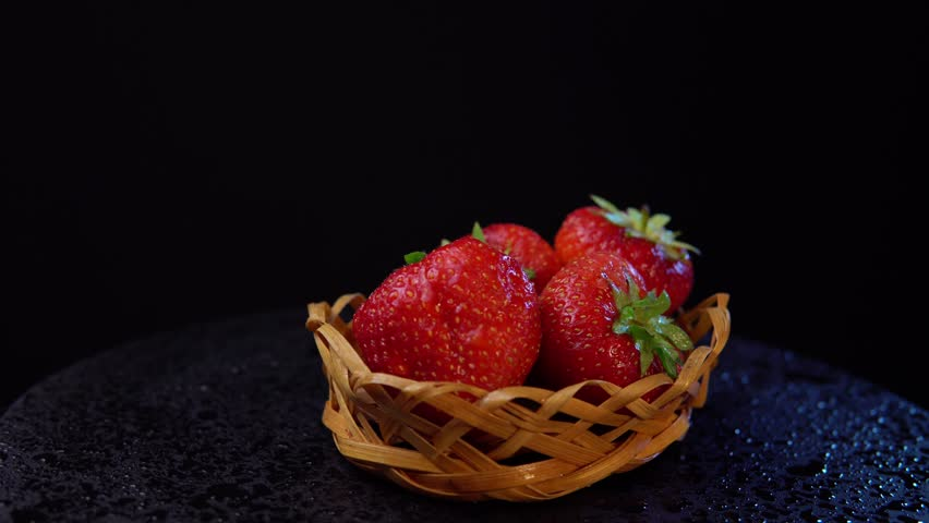 Fresh, ripe juicy strawberries in a wicker basket revolve under water splashes. Red berries rotate counter-clockwise against a black background close-up.