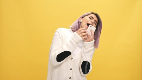 Cheerful woman in warm cardigan and headphones listening music by smartphone and sings over yellow background