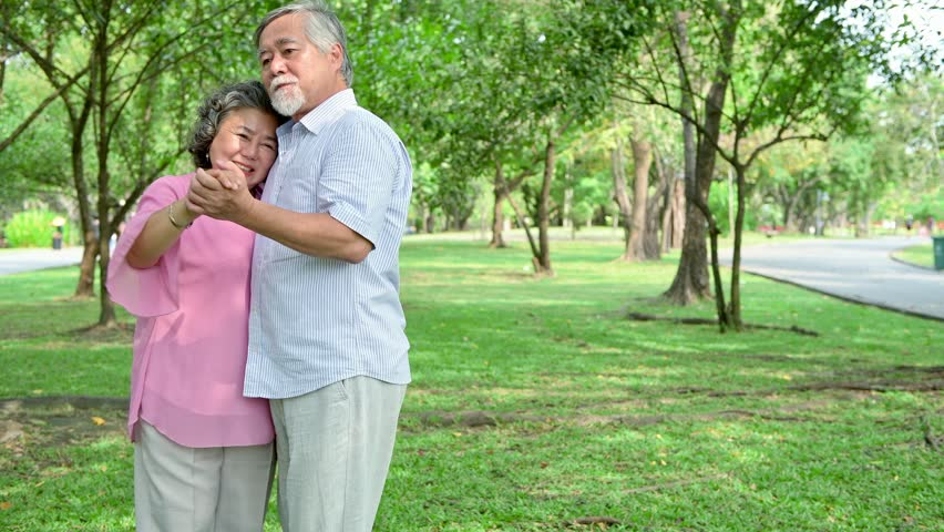 Sweet senior couple dancing in park. Old asian man and woman dancing together in park standing up. Senior lifestyle concept. | Shutterstock HD Video #1015773946