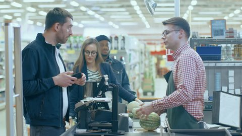 At the Supermarket: Checkout Counter Customer Pays with Smartphone for His Items. Big Shopping Mall with Friendly Cashier, Small Lines and Modern Wireless Paying Terminal System. Shot on RED EPIC-W 8K