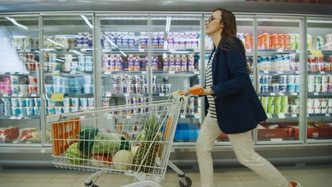 Beautiful Young Woman Pushes Shopping Cart full of Healthy Products Through Frozen Goods and Dairy Section of the Supermarket. Moving Side View Shot. Shot on RED EPIC-W 8K Helium Cinema Camera.