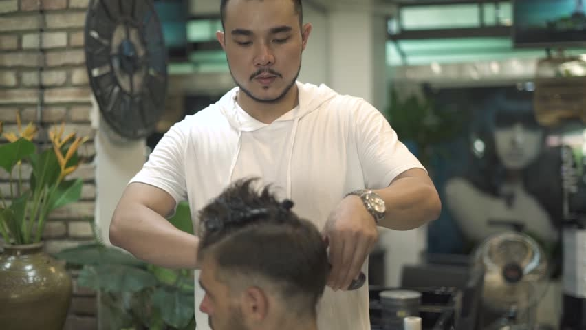 Asian hairdresser doing male haircut with electric shaver. Man getting haircut in barber shop. Professional hairstylist cutting hair in male salon. Man hairdressing with electric razor