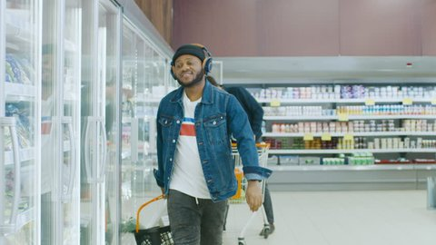 At the Supermarket: Stylish African American Guy with Shopping Basket Chooses Products in the Frozen Goods Section of the Store. He Opens Big Glass Door Fridge. Slow Motion. Shot on RED EPIC-W 8K.