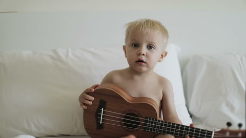 A little blond boy looks at the camera and plays ukulele. A cute naked baby sits on a bed and holds a musical instrument. Slow motion.