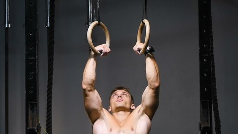 strong bodybuilder muscular athletic man with jump rope and gymnastic rings pumping up muscles workout bodybuilding concept background - muscular bodybuilder handsome men doing exercises in gym naked