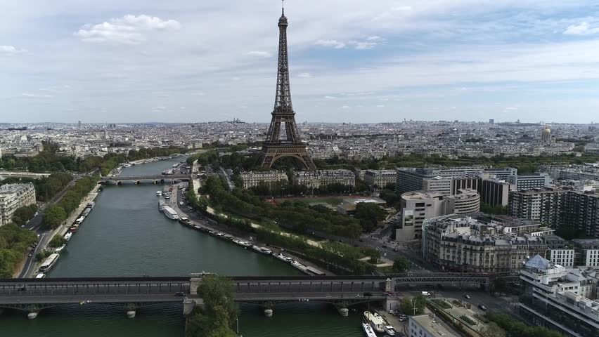 Aerial footage moving slowly towards Eiffel Tower is a wrought iron lattice structure on Champ de Mars in Paris France the building is named after the engineer whose company designed and built it 4k | Shutterstock HD Video #1015827766