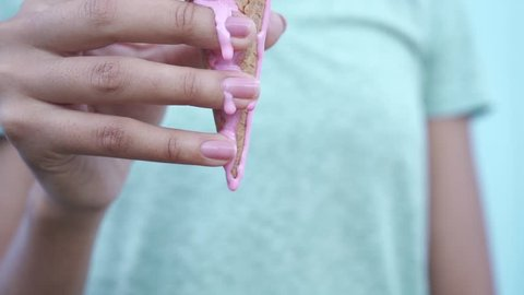 pink melting ice cream flows down in slow motion on the fingers of a black girl at a blue background