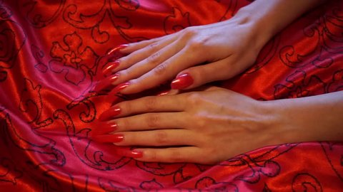 Long red polished Nails and red silk fabric