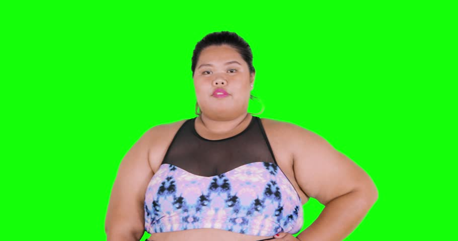 Attractive overweight female model posing at camera in the studio, shot in 4k resolution with green screen background | Shutterstock HD Video #1015834726