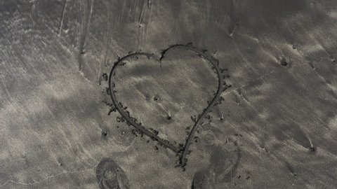Heart shape traced on beach sands. Top down view.