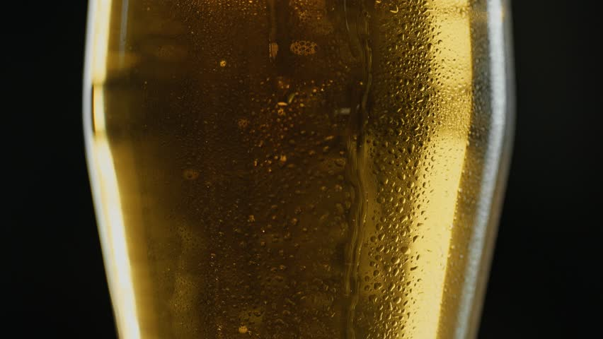 Misted mug of cold light kraft beer, drops flow down the glass, in bar or pub. Close up panorama shot. Isolated black background. Slow motion