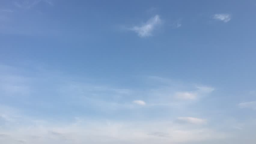 White clouds disappear in the hot sun on blue sky. Loop features time lapse motion clouds backed by a beautiful blue sky. Time-lapse motion clouds blue sky background and sun.   Shutterstock HD Video #1015919386