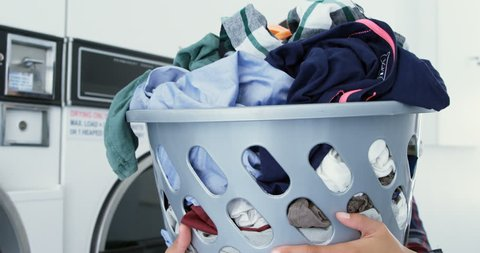 Close-up of woman carrying clothes in laundry basket at laundromat 4k