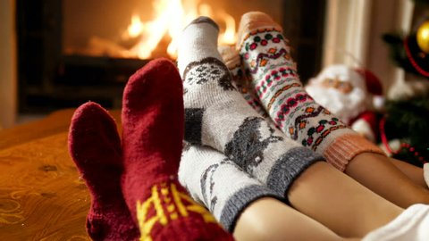 Closeup 4k footage of family feet in woolen socks lying by the burning fireplace at night