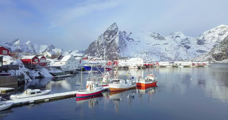Aerial panorama drone view of beautiful Lofoten Islands winter scenery with traditional fishing boats lying in harbor of famous Hamnoy village on a cold sunny day, Norway, Scandinavia, northern Europe