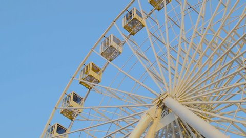 Ferris wheel shot against blue sky. Warm colors, daylight.