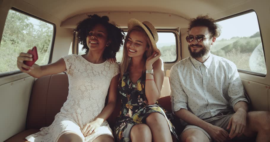 Selfie time in a retro vintage bus , two charismatics girls and one man taking pictures using a phone , they wearing boho style clothes. #1015951066