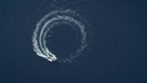 Aerial view of a boat driving in circles forming waves around in Greece.