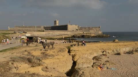 Carcavelos, Portugal - Sept 5, 2018: Beachgoers relax on the beach near the 16th Century Saint Julian Fortress at Carcavelos beach near Lisbon, Portugal