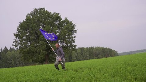 man is running with a flag of the European Union in country landscape. Standard Bearer