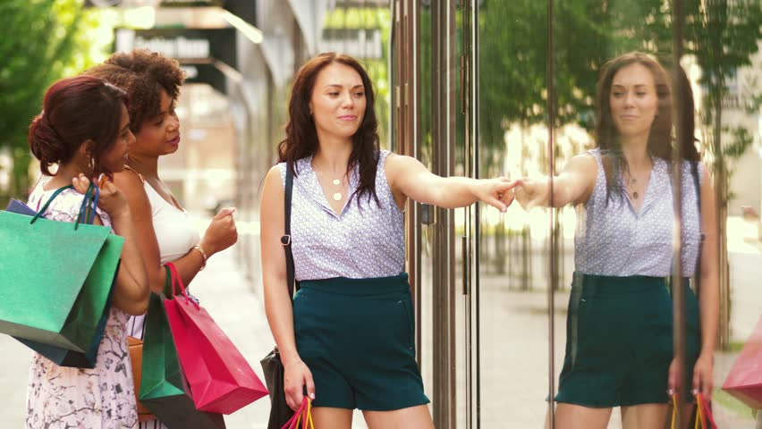 Sale, consumerism and people concept - happy young women with shopping bags pointing finger to shop window in city | Shutterstock HD Video #1015997356