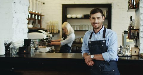 Portrait shot of the handsome smiled waiter standing and leaning on the bar while blond attractive waitress preparing coffe behind.