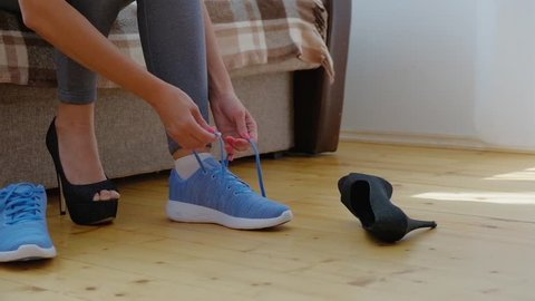 Woman changing high heels shoes before training, slow motion video