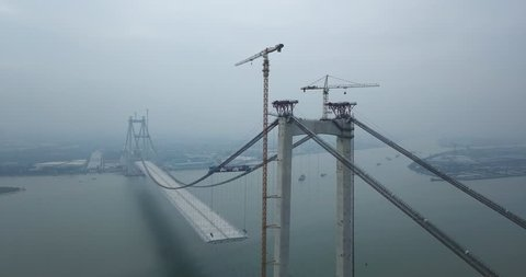 Mega bridge construction over the river in China Asia, with stationary boats anchored on the river.