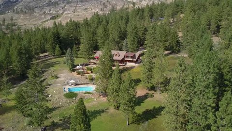 Large log house home and pool in the forest filmed in circling aerial drone view. large building with terrace and tennis court behind pine trees. Hillside property in the wild. Dream house in forest