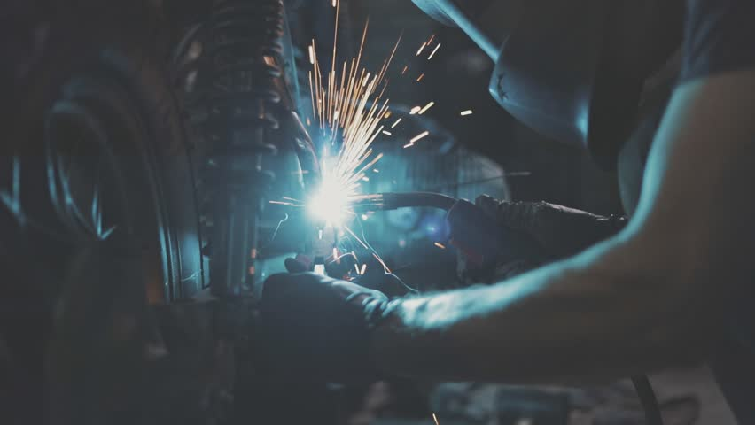 Automaster weld the frame of a custom motorcycle in the garage. Sparks welding machine. Protective face mask. 4k video