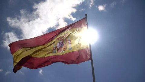 Close-up of Spain flag in front sun and blue sky slow waving on wind