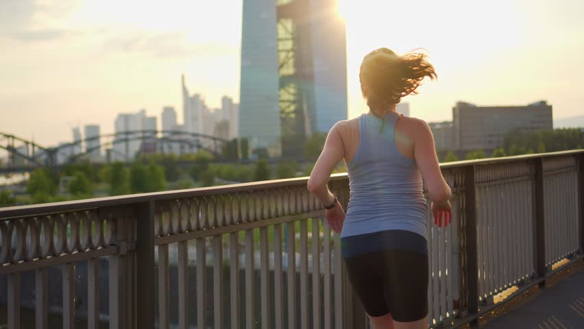 a pregnant woman goes in for sports, runs across the bridge against the backdrop of a large city of Frankfurt in a beautiful sunset. a healthy lifestyle for the future child #1016099296