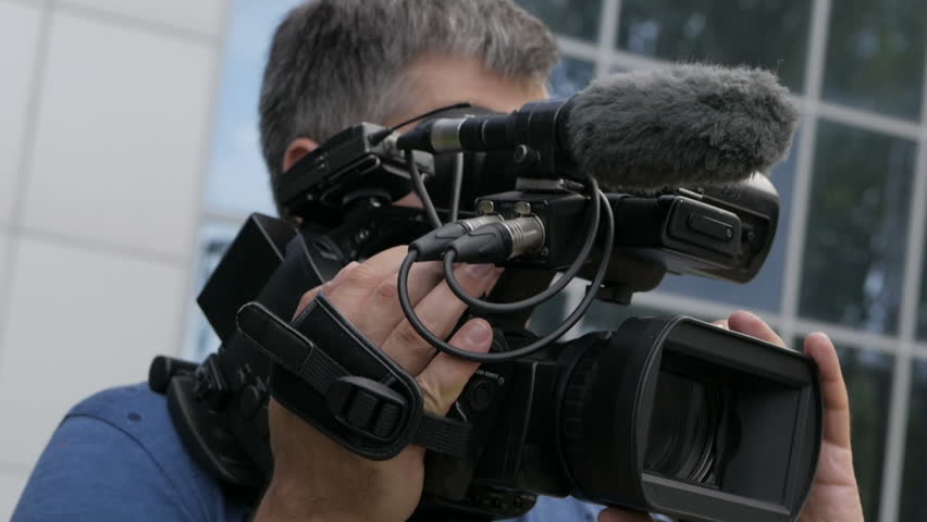 Male hands hold and move a large professional video camera in a close-up view. | Shutterstock HD Video #1016139916