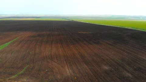 Tractor Ploughing Field Aerial Video. Tractor Plow Farm Field 4K Drone Flight. Cultivation Soil: Plowing Field Harvesting Aerial Top View Video. Fresh Ploughed Field
