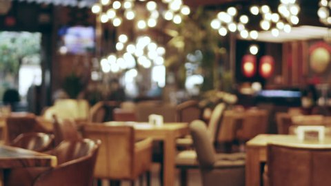 Blurred picture of the interior of a large beautiful restaurant with bright lighting, of the entrance. Tables with chairs are waiting for visitors for dinner. Visitors choose their own table