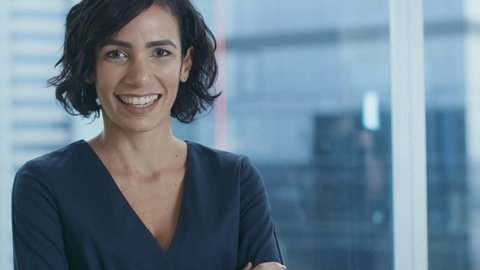 Portrait of the Successful Businesswoman Crossing Her Arms and Smiling. Beautiful Female Executive Standing in Her Office. Shot on RED EPIC-W 8K Helium Cinema Camera.