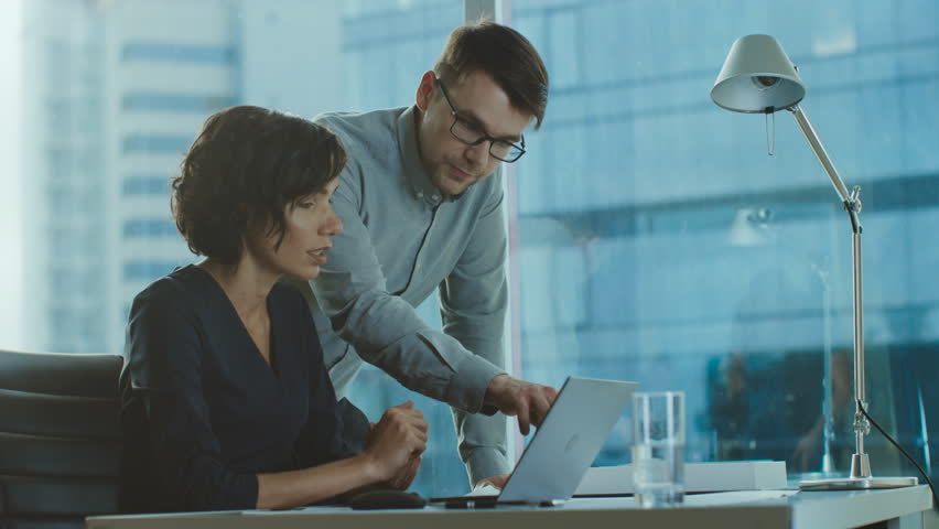Beautiful Businesswoman Listens to Professional Advisor in Her Office, They Discuss Data Show on a Laptop. Smart Young Businesspeople Working in Finance. Shot on RED EPIC-W 8K Helium Cinema Camera. | Shutterstock HD Video #1016145916