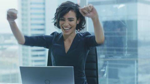 Back View Shot of the Beautiful Businesswoman Sitting at Her Office Desk, Raising Her Arms and Claps in a Celebration of a Successful Job Promotion. Shot on RED EPIC-W 8K Helium Cinema Camera.