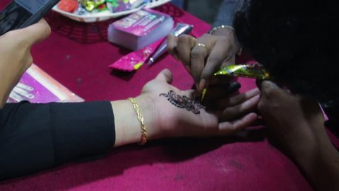 A woman is having a decorative floral henna design put on her hand.