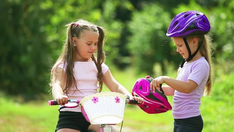 The older sister helps the younger girl to put on a safe helmet before riding a bike on a Sunny summer day in nature and give five to each other . Safety, sports, recreation