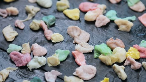 chewed chewing gum of different colors on a black background. VIDEO rotation