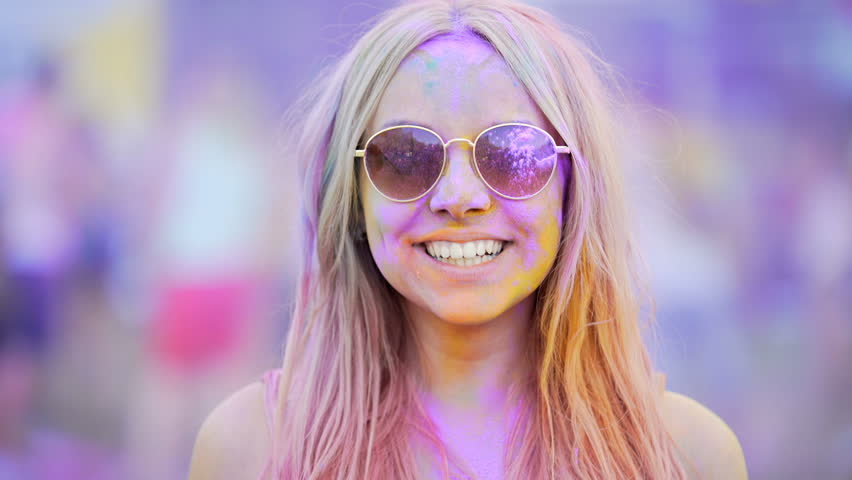 Girl in sunglasses making thumbs-up, looking through rose-colored spectacles