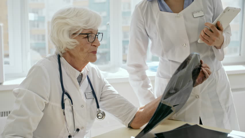 Senior female doctor in lab coat and eyeglasses sitting at desk, looking at x-ray image and discussing diagnosis with female assistant | Shutterstock HD Video #1016194846
