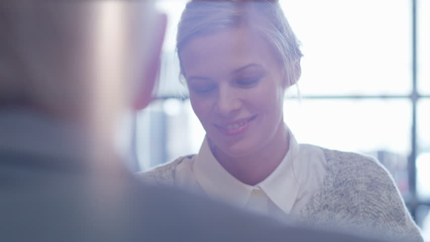 Handheld shot of businesswoman discussing with male coworkers in creative office