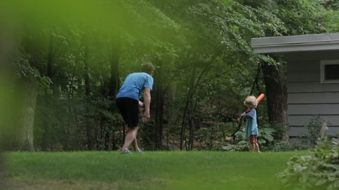 Cheerful father and son playing baseball at yard