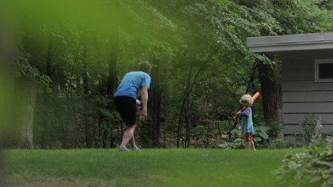 Cheerful father and son playing baseball at yard