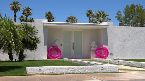 CIRCA 2018 - Establishing shot of a classic mid century modern deco style home in Palm Springs, California with pink innertubes in entry way.