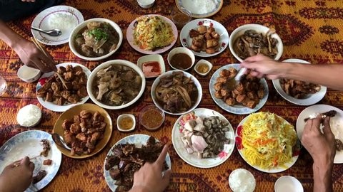 Chinese new year festival concept.Group of people in family eating lunch, with Food offerings on chinese new year festival, after pray of god, or ancestor worship, top view.