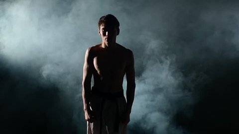Karate man with a naked torso and a black belt. doing various exercises hands, smoke. close up, Slow motion