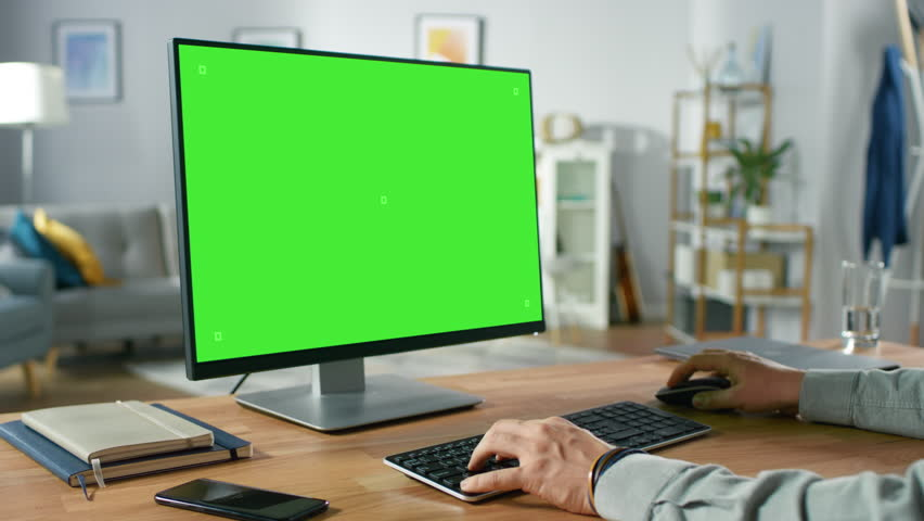 Over the Shoulder Shot of Professional Freelancer Working on Green Mockup Screen Personal Computer From Home. Man's Hands Typing, He's Browsing Through the Internet, Using Computer In Living Room. | Shutterstock HD Video #1016261986
